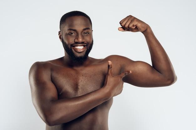 Lächelnder mann des afroamerikaners mit bloßem kasten.
