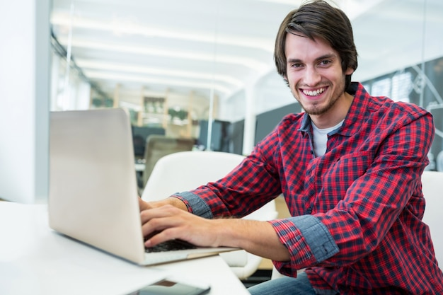 Lächelnder mann eingabe auf einem laptop