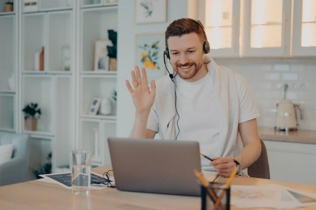 Lächelnder mann freiberufler mit kopfhörern winkt seinem kollegen zu und hat online-meetings, arbeitet aus der ferne von zu hause aus, glücklicher kerl, der auf die laptop-webcam schaut und jemanden begrüßt. freiberufliches konzept