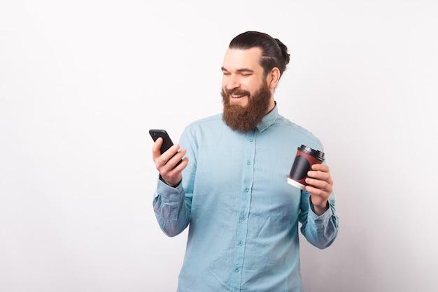 Lächelnder mann hält seine tasse und sein telefon zum mitnehmen auf weißem hintergrund.