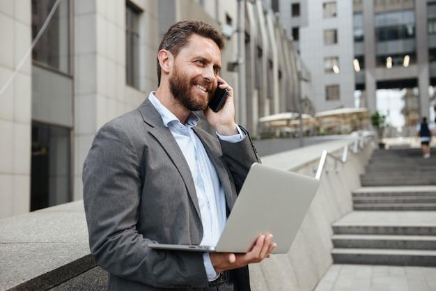 Lächelnder mann im grauen anzug, der offenen silbernen laptop hält und auf handy spricht, während er nahe bürogebäude steht
