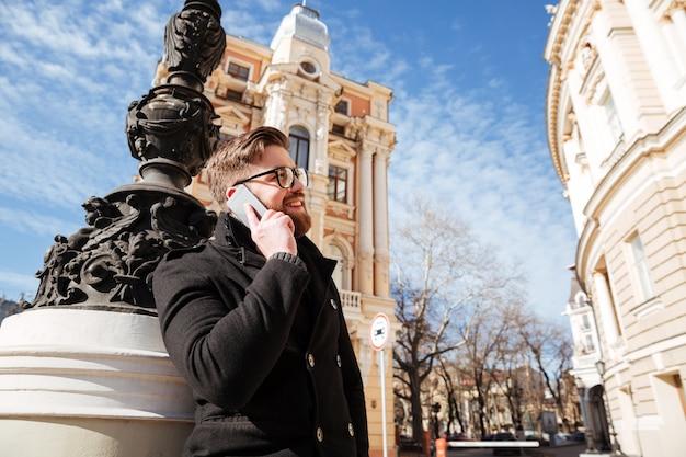 Lächelnder mann im mantel, der am telefon auf der straße spricht