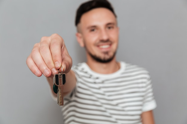 Lächelnder mann im t-shirt, das schlüssel an der kamera zeigt
