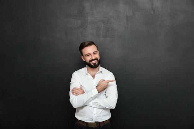 Lächelnder mann im weißen hemd, das auf kamera mit dem breiten lächeln, zeigefinger über dunkelgrauem kopienraum beiseite zeigend aufwirft