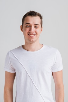 Lächelnder mann im weißen t-shirt, das kamera betrachtet