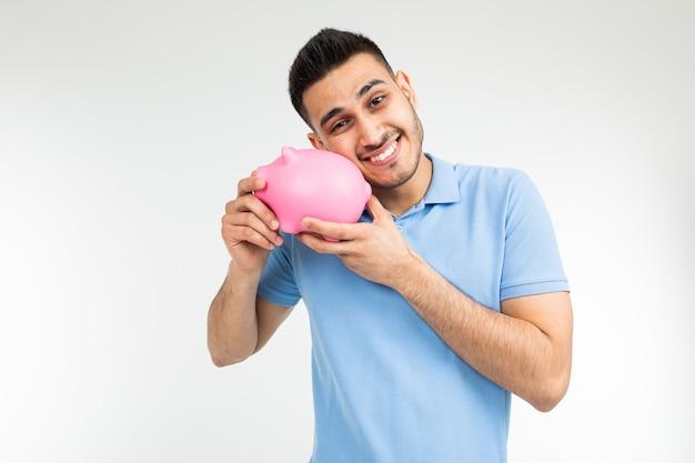 Lächelnder mann in einem blauen t-shirt umarmt ein sparschwein auf einem weißen hintergrund mit kopienraum