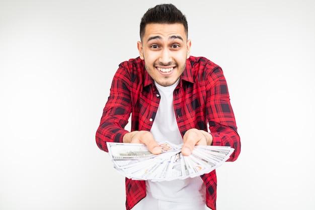 Lächelnder mann in einem karierten hemd, das einen haufen geld auf einem weißen hintergrund heraushält