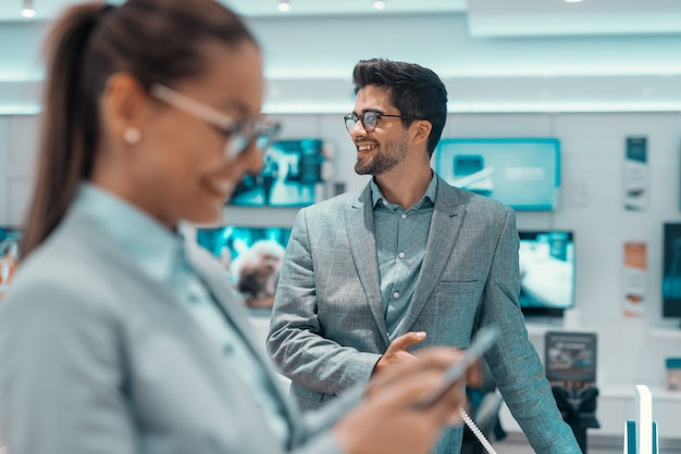 Lächelnder mann in formeller kleidung, der im technologieladen steht und wegschaut