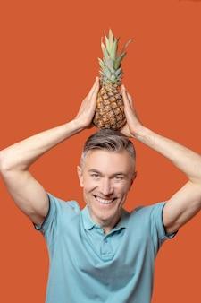 Lächelnder mann mit ananas auf dem kopf