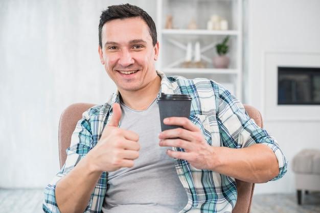 Lächelnder mann mit dem daumen, der zu hause schale des getränks auf stuhl hochhält