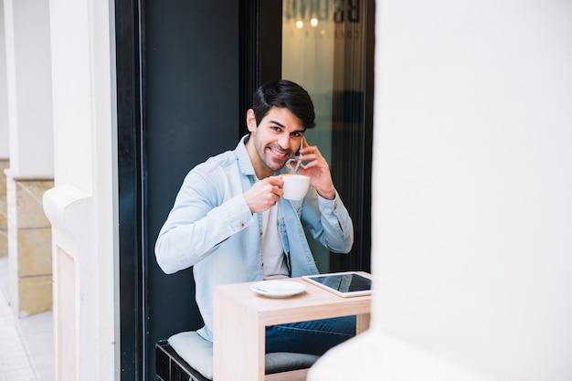 Lächelnder mann mit der schale, die auf smartphone spricht