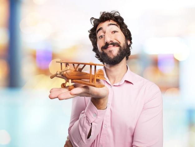 Lächelnder mann mit einem hölzernen flugzeug