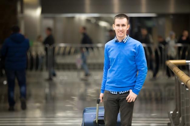 Lächelnder mann mit einem koffer
