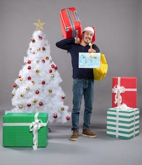 Lächelnder mann mit gelbem rucksack, der karte nahe weihnachtsbaum auf grau hält