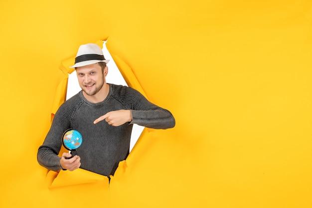 Lächelnder mann mit hut, der einen kleinen globus hält und einen kleinen globus in einer zerrissenen gelben wand zeigt