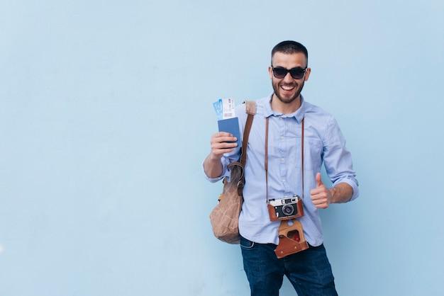 Lächelnder mann mit kamera um seinen hals, der flugticket hält und daumen herauf die geste steht nahe blauer wand zeigt