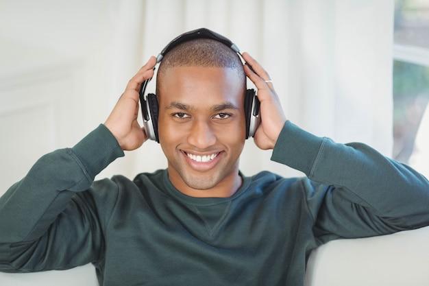 Lächelnder mann mit kopfhörern auf dem sofa, welches die kamera betrachtet