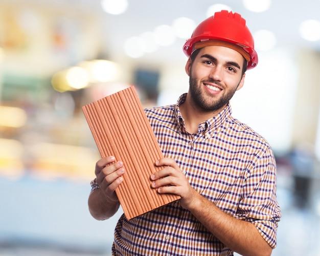 Lächelnder mann mit rotem helm und einem ziegelstein