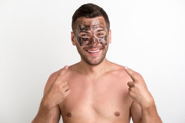 Lächelnder mann mit schwarzer maske zeigend auf sein gesicht gegen weißen hintergrund