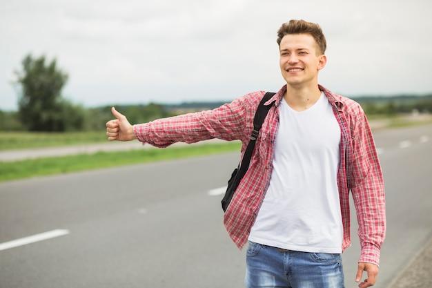 Lächelnder mann mit seinem rucksack, der auf straße per anhalter fährt