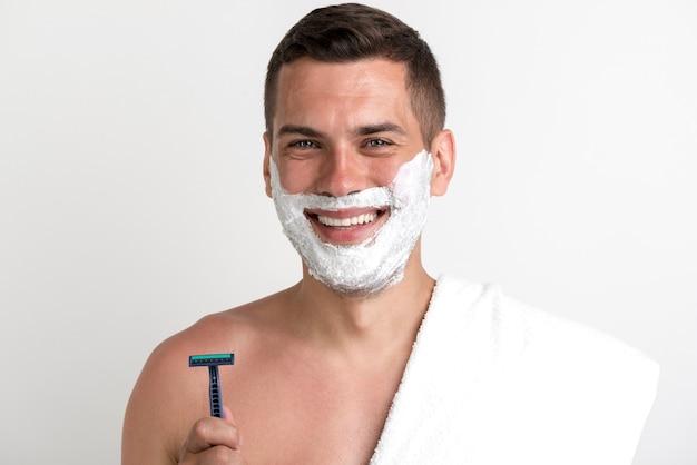 Lächelnder mann mit tuch trug den rasierschaum auf, der das rasiermesser hält, das kamera betrachtet