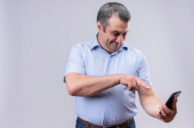 Lächelnder mann mittleren alters, der blaues vertikales gestreiftes hemd trägt, das sein handy betrachtet und mit dem finger darauf zeigt, während er auf einem weißen hintergrund steht