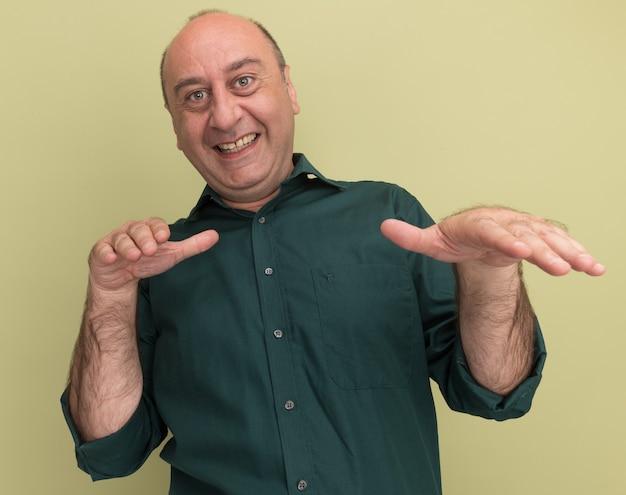 Lächelnder mann mittleren alters, der grünes t-shirt trägt, das hände an der kamera lokalisiert auf olivgrüner wand heraushält