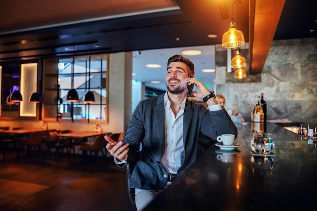 Lächelnder mann mittleren alters, der in einer bar eines schicken hotels sitzt und telefoniert.