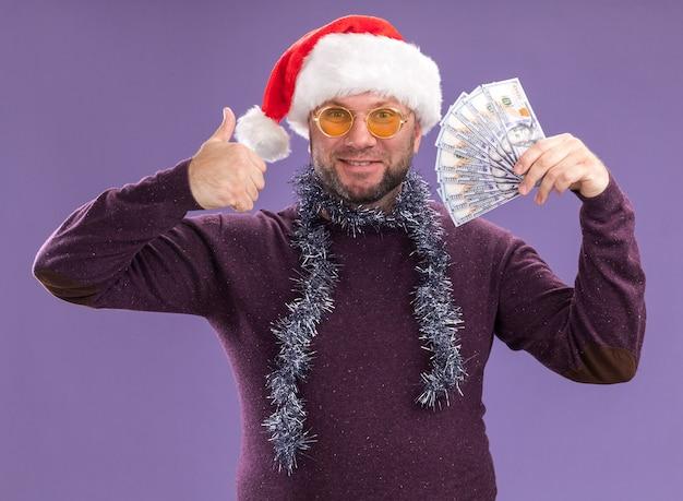 Lächelnder mann mittleren alters, der weihnachtsmütze und lametta-girlande um den hals mit brille trägt, die geld hält, das daumen oben auf lila wand zeigt