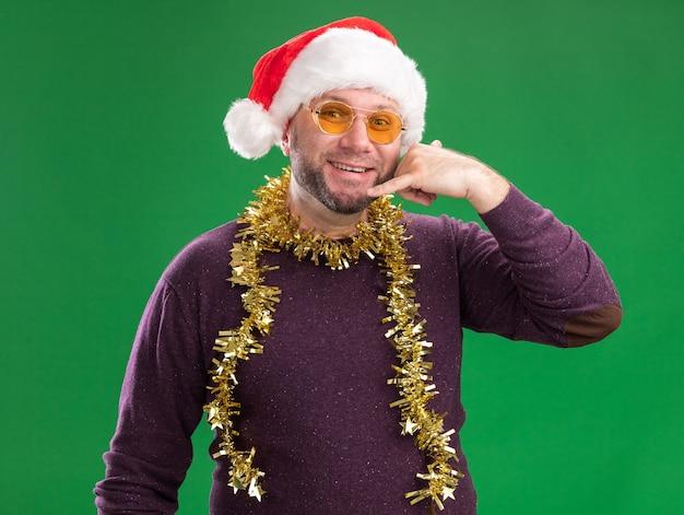 Lächelnder mann mittleren alters, der weihnachtsmütze und lametta-girlande um den hals mit brille trägt, die kamera betrachtet, die rufgeste lokalisiert auf grünem hintergrund tut