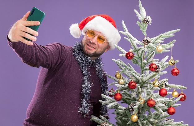 Lächelnder mann mittleren alters, der weihnachtsmütze und lametta-girlande um den hals mit gläsern trägt, die nahe verziertem weihnachtsbaum stehen und selfie lokalisiert auf lila wand nehmen