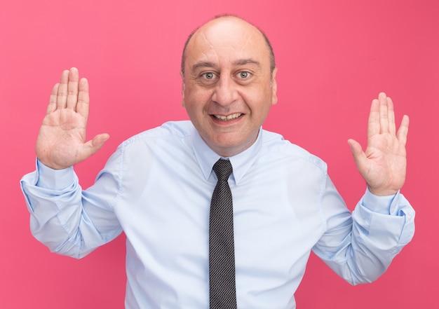 Lächelnder mann mittleren alters, der weißes t-shirt mit krawattenverbreitungshänden auf rosa wand isoliert trägt