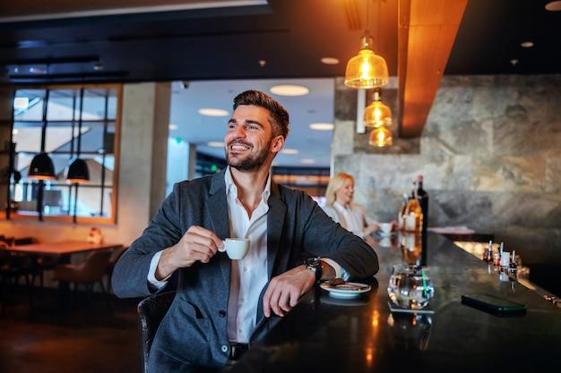 Lächelnder mann mittleren alters in abendgarderobe, der in der bar sitzt und seinen morgenkaffee trinkt.