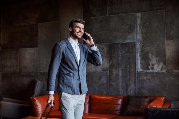 Lächelnder mann mittleren alters in einem anzug, der in der lobby eines schicken hotels spazieren geht und ein angenehmes telefongespräch führt. er zieht seinen koffer.