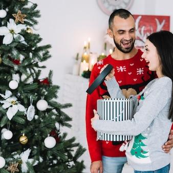 Lächelnder mann nahe frau mit geschenk