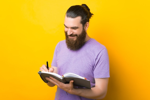 Lächelnder mann schreibt eine idee in sein tagebuch, während er über gelbem hintergrund steht.