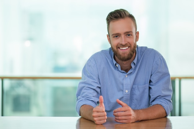 Lächelnder mann sitzt am tisch eines cafes und gestikulieren
