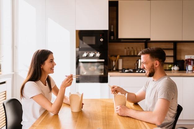 Lächelnder mann und frau, die zu hause zusammen zu mittag essen