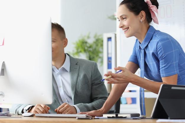 Lächelnder mann und frau diskutieren geschäftsprozesse am arbeitstisch erfolgreiches geschäftsteam