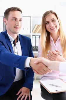 Lächelnder mann und frau geben sich im büro die hand als hallo