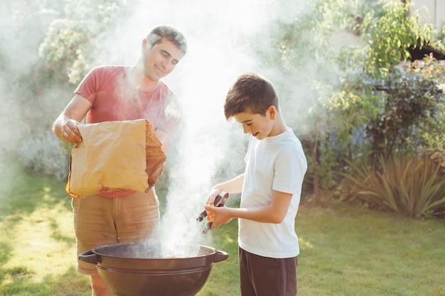 Lächelnder mann und junge, die kohle in grill am park einsetzen