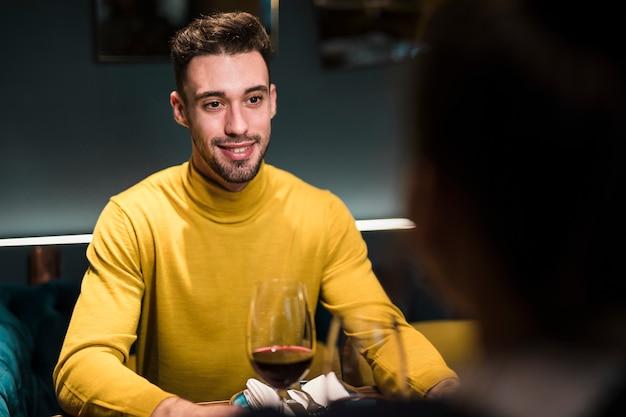 Lächelnder mann und person, die am tisch mit gläsern wein sitzen