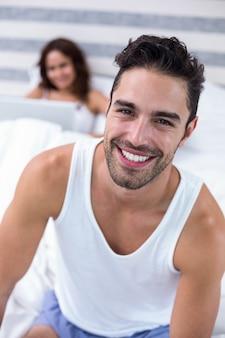 Lächelnder mann während frau, die auf bett sitzt