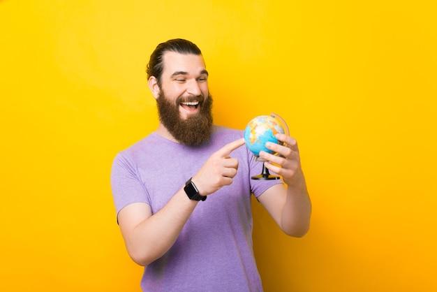 Lächelnder mann zeigt auf einen kleinen globus über gelbem hintergrund.