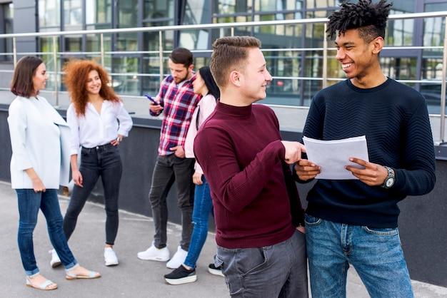 Lächelnder mann zwei, der über dokument mit ihren freunden stehen am hintergrund sich bespricht