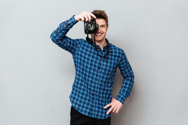 Lächelnder mannfotograf, der kamera schaut