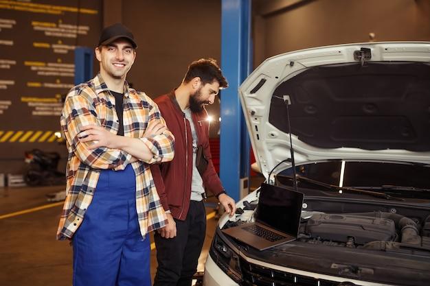 Lächelnder mechaniker, der mit gekreuzten händen in die kamera schaut, während der kunde den laptop im hintergrund in der werkstatt anschaut