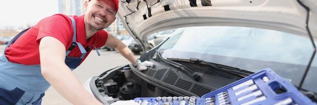 Lächelnder mechaniker in uniform, der auto mit werkzeugen repariert