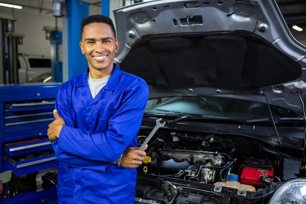 Lächelnder mechaniker mit verschränkten armen und schlüssel