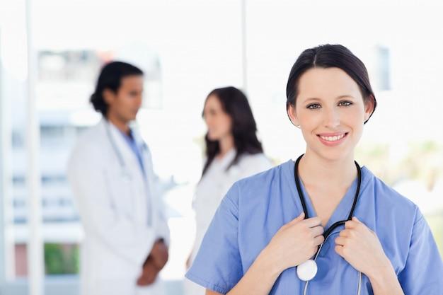 Lächelnder medizinischer internierter mit ihrem haar band zurück, stehend vor ihrem team